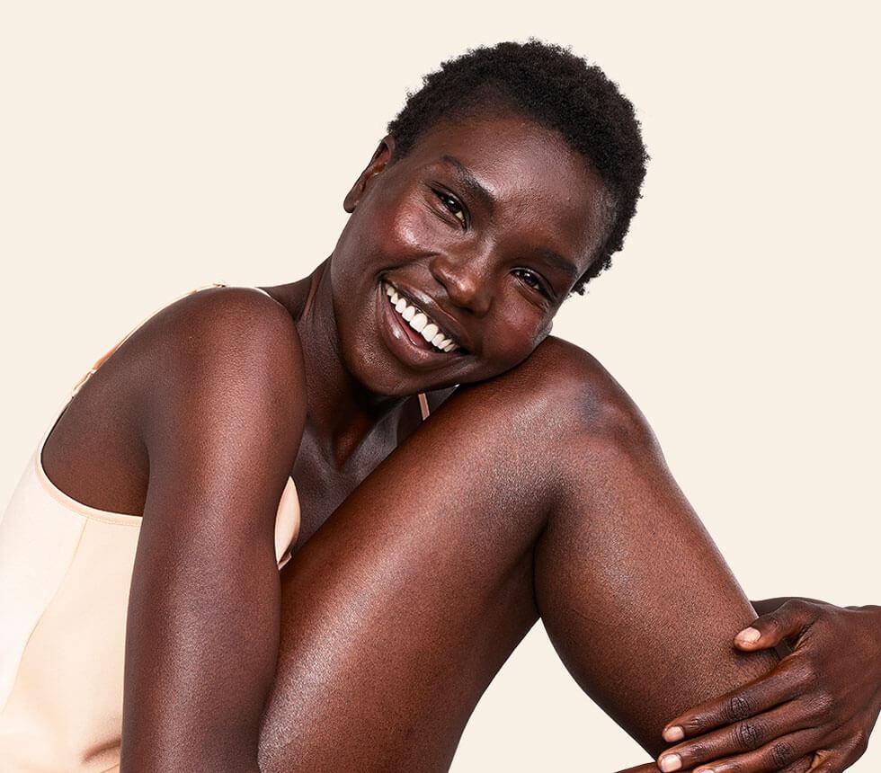 pele radiante no corpo e no rosto em mulher aveeno a sorrir
