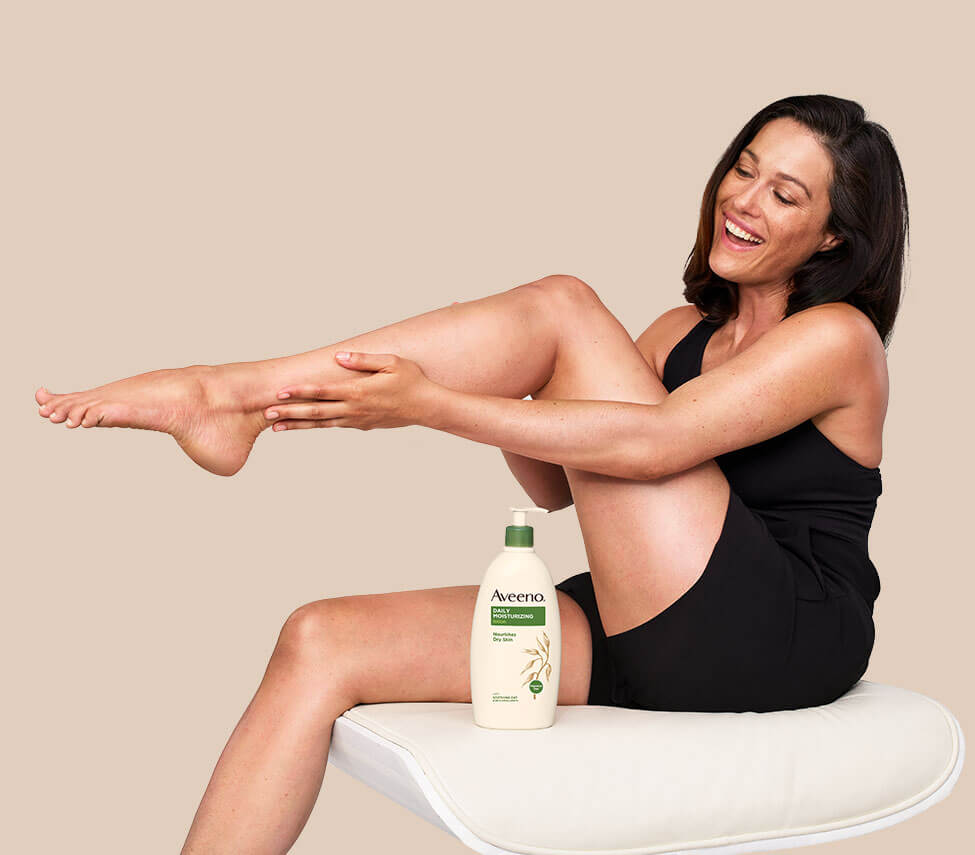 woman using aveeno body lotion for dry skin on legs