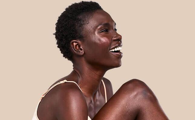 mulher a sorrir com pele radiante na cara e no rosto da aveeno