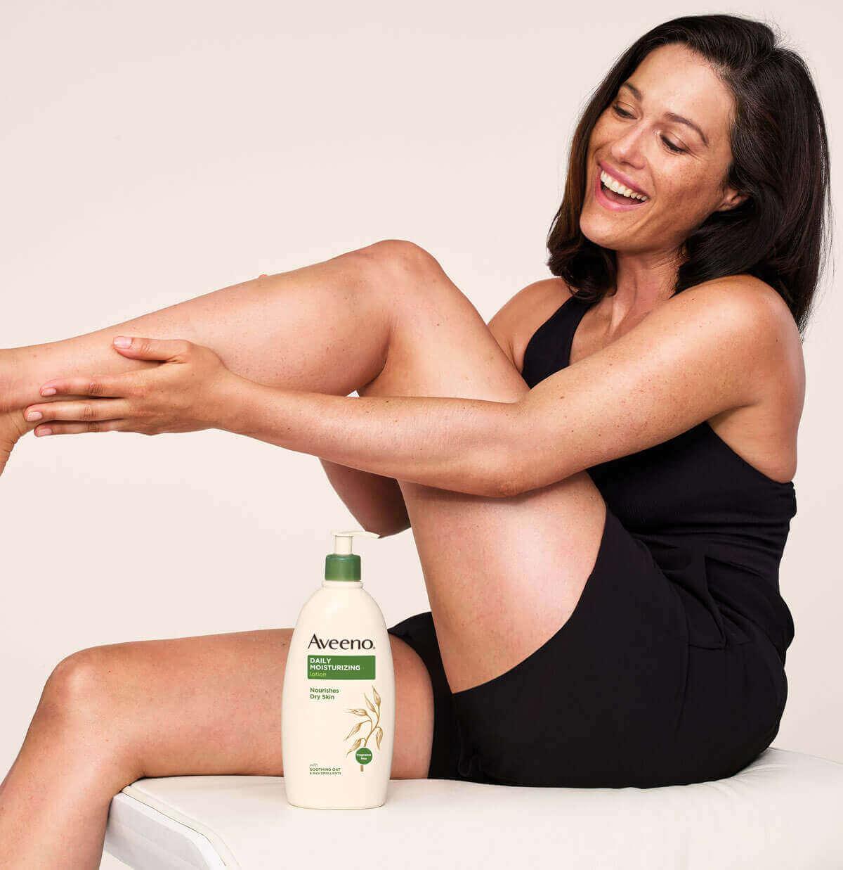 donna che utilizza una crema corpo aveeno per pelli secche sulle gambe